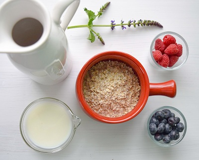Oats in a bowl, a cup of milk and two bowls with staw berries and blue berries